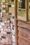 Wavy random rough sawn boards meet the brick fireplace section