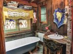 Rustic bathroom, with son Daniel's hand-tiled floor and Kathleen's glowingly fanciful mirror